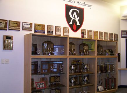 Trophy cases and team photos are displayed in the athletic center lobby.
